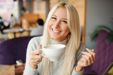 Cheerful happy blond woman in cafe drinking morning coffee and smiling