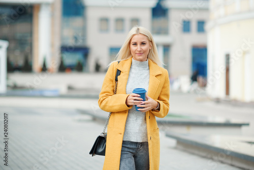 obraz lub plakat Coffee on the go. Beautiful young blond woman in bright yellow coat holding coffee cup and smiling while walking along the street