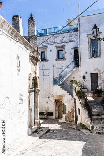 Street view of white houses in old Italian village  - 240826284