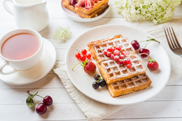 Homemade waffles with summer berries on a plate. A Cup of tea on a light table. Selective focus
