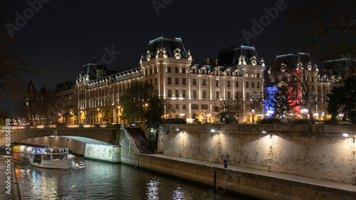 obraz PCV Building facades in front of the Seine with a boat in Paris illuminated in the colours of France