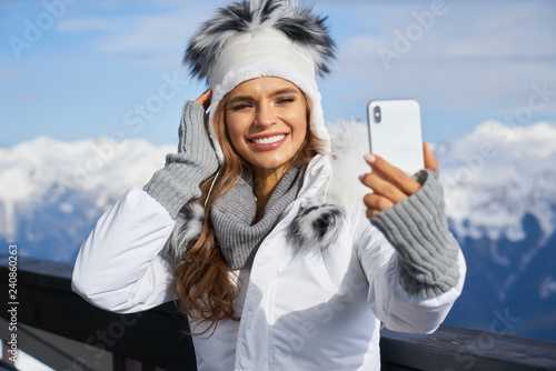 Leinwanddruck Bild Woman skier making selfie photo on the background of snowy high mountains and