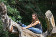 Smiling flexible woman posing with urban clothing on tree trunk in forest. Young lady in paschimottanasana yoga pose outdoors in nature