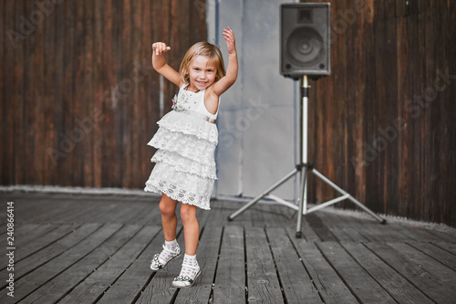Little girl in white dress dancing outdoors at the old wooden stage