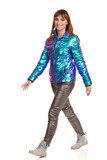 Young Woman Is Walking In Vibrant Down Jacket And Shiny Pants - 240870444