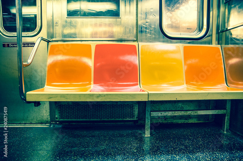 View inside New York City subway train car with vintage orange, yellow and red color seats