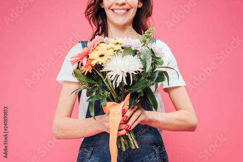 partial view of woman holding flower bouquet isolated on pink