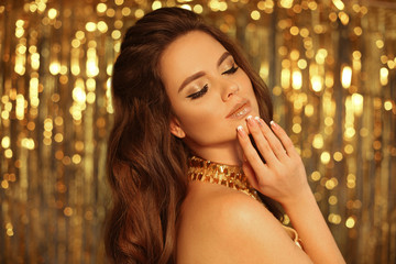 Glamour eye shadows Makeup. Fashion Beauty Girl Portrait Isolated on golden Christmas lights garlands bokeh background.  Alluring brunette with sensual glittering lipstick looking at camera. © Victoria Andreas