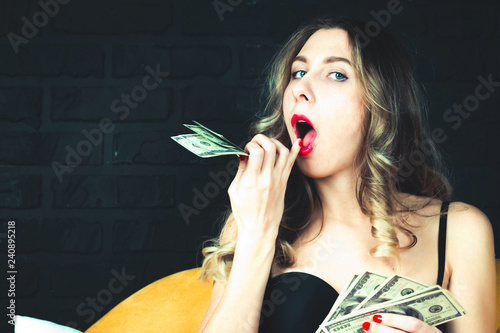 Sexy young girl wipes her mouth and counts dollars. Concept of unexpected ways to earn money - 240895218