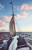 Old schooner sailing at sunset, travel and adventure concept, color toned picture. © MaciejBledowski