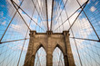 Classic view of the steel cable pattern and rough brick details of a stone tower of the Brooklyn Bridge under soft picturesque clouds