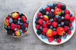 Leinwanddruck Bild - Fresh berry salad on blue dishes. Vintage wooden background.