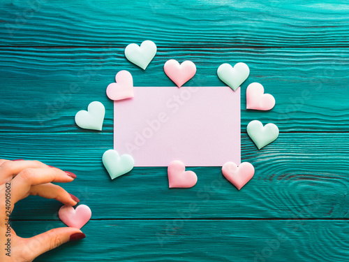 Pink blank card on wooden background with hearts