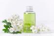 Leinwanddruck Bild - a cosmetic bottle with fresh flowers, selective focus