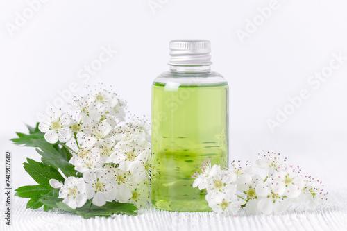 Leinwanddruck Bild a cosmetic bottle with fresh flowers, selective focus