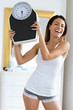 Leinwanddruck Bild - Happiness young woman holding weigh scale while looking at camera at home.