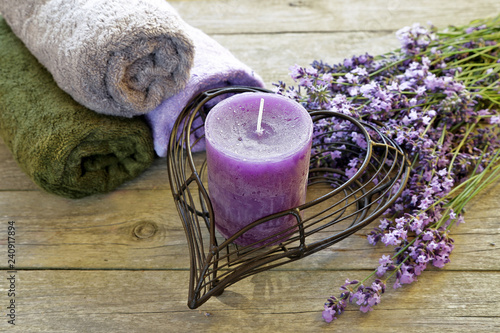 Lavender flowers with candle and towel on wooden background  - 240917894