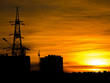 Leinwanddruck Bild - Bright orange sunset. Houses and industrial constructions against a fiery sunset. Cityscape, industrial landscape.