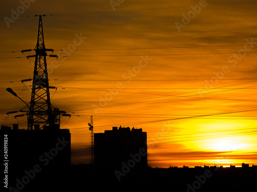 Leinwanddruck Bild Bright orange sunset. Houses and industrial constructions against a fiery sunset. Cityscape, industrial landscape.