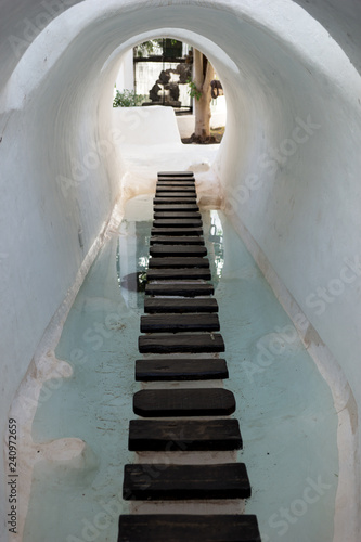 Wooden footpath through the white arched tunnel