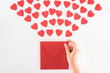 partial view of woman holding envelop under dozen red heart symbols isolated on white, st valentine day concept