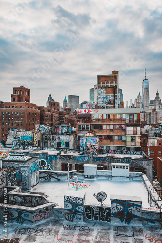 Graffiti on Manhattan Buildings, rooftop, skyscraper and cloudy blue sky