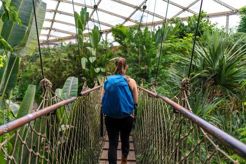 Girl with a backpack walking over a suspension bridge in the jungle