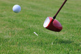 teeing off a golf ball with a driver club