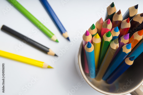 Set of colorful wooden pencils in cup on white background