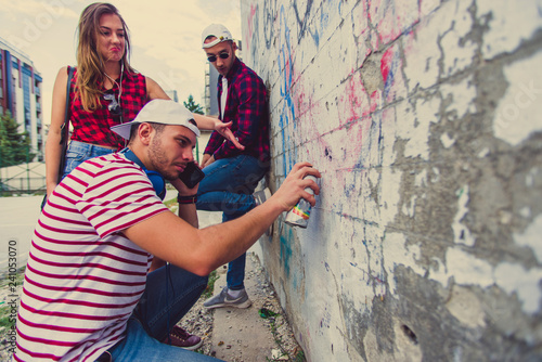 Urban guy drawing graffiti on the wall with his friends