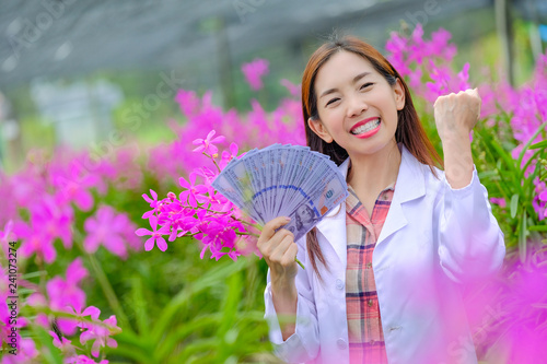 Researchers, women, are glad to succeed in pink orchid orchards in the garden for export. - 241073274
