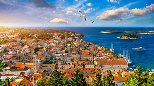 Leinwanddruck Bild Hvar town with seagull's flying over city, famous luxury travel destination in Croatia. Boats on Hvar island, one of the many Islands near Dubrovnik and Korcula on the Dalmatian Coast of Croatia.