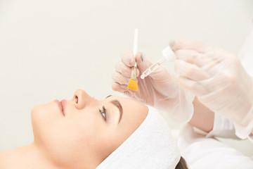 Young woman cleaning face skin in salon. Retinol peel with brush. Acid organic peeling