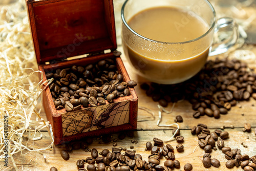 A glass cup of coffee with milk in the morning, next to roasted coffee beans, on a wooden, natural, rustic table