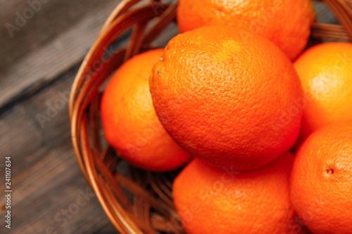 Fresh oranges in a basket on old vintage wooden table