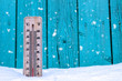 Wooden thermometer on a background of green boards and white snow