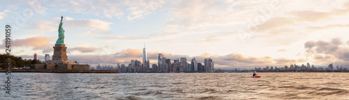 Panoramic view of the Statue of Liberty and Downtown Manhattan in the background during a vibrant cloudy sunrise. Taken in Jersey City, New Jersey, United States. - 241191059