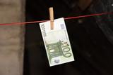 Ein Euro Geldschein an einer Wäscheleine als Symbol für die Gelwäsche - 241195021
