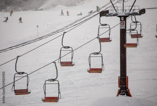 obraz PCV Empty chair lifts on snowy mountain with snowboarders and skiers in background