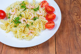 Cooked spiral pasta with shrimps, cheese, cherry tomatoes close-up