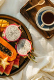 Flatlay with cup of coffee or tea on wooden tray and tropical fruit plate with notebook and pen on side on white sheets, selective focus - 241214631