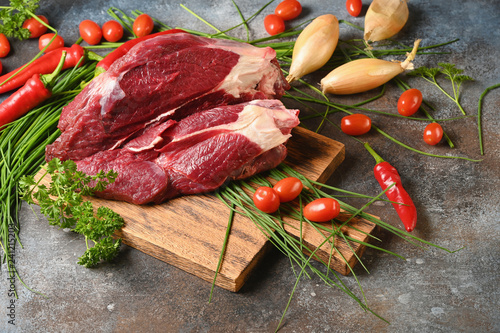 Fresh dark meat with ingredients for cooking on brown wooden cutting board. Hunting composition. Wildanimal hunting. - 241215203