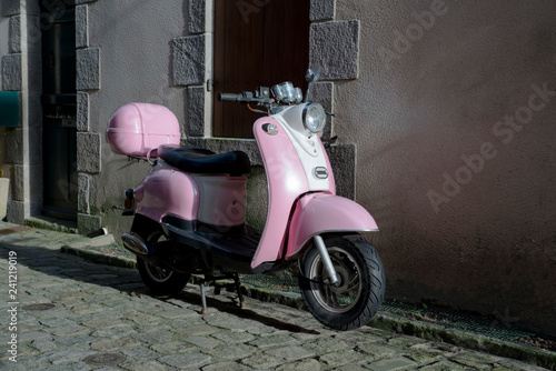A pink scooter parked in a paved street in front of a wall