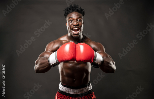 Muscular African American Black male sweaty boxer does an aggressive scream towards the camera  with dramatic lighting with a black background
