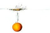 Fresh fruit dives into cold water with splash and bubbles