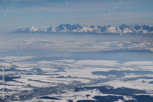 Jagged snowy High Tatra peaks above hazy Podhale basin in winter sunshine, Lomnica Lodowy Szczyt Gerlach Rysy, Tatry Wysokie and Bielskie Zakopane Malopolskie Poland Slovakia Eastern /Central Europe