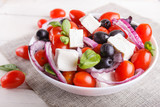 Greek salad with fresh cherry tomatoes, feta cheese, black olives, basil and onion on white wooden background. - 241244671