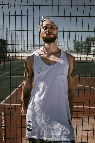 Young man with white headband dressed in the white t-shirt, black leggings and blue shorts stands leaning on the playground fence outside on a sunny day