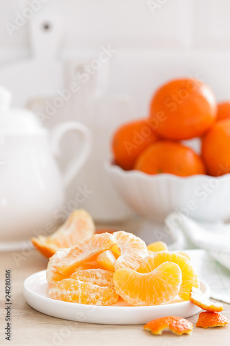 Foto Murales Tangerines. Sweet tasty peeled tangerines on plate on white kitchen background closeup. Healthy and delicious vegan, vegetarian food.