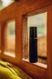 Essential oils roll on perfume in a dark brown glass bottle among nature background. Beauty blogging, salon treatment. Toned image - 241292029